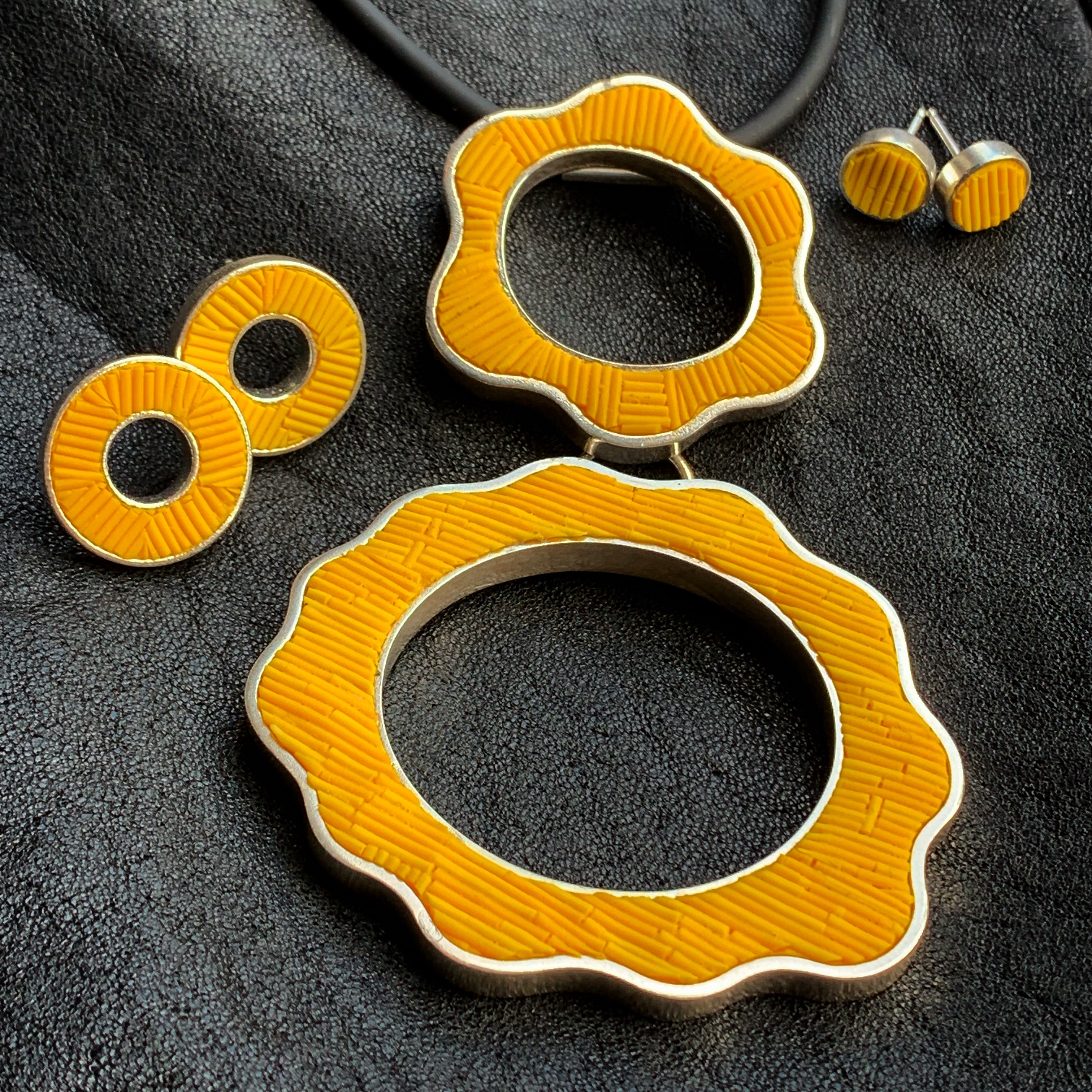 Polymer inlay in sterling silver. Necklace, post earrings, and tiny stud earrings. Work by Tegan Wallace.